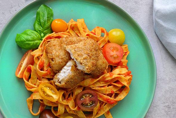 Sprøbakte fiskefileter ligger på tagliatelle i pastasaus med små tomater og salat. Godt fiskemåltid for barn