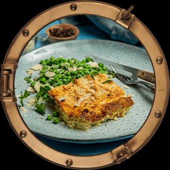 Stekte erter med parmesan og fiskegrateng på tallerken,  innrammet i koøye