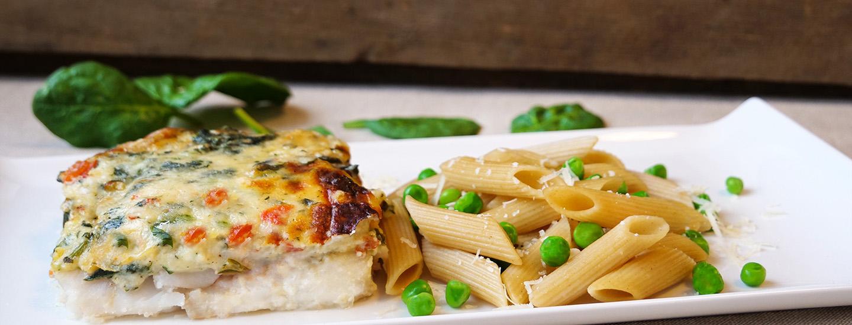 Fiskefilet med bladspinatsaus og ost, servert med fullkornspenne og erter (produktbilde)