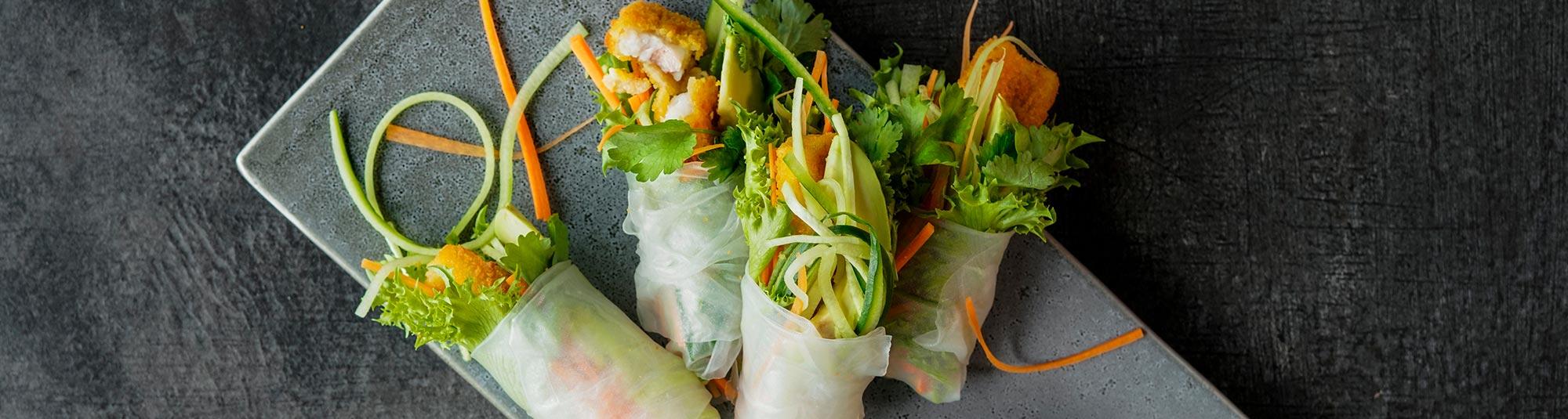 Fiskepinner og grønnsaker i ferske vårruller på kjøkkenbenken