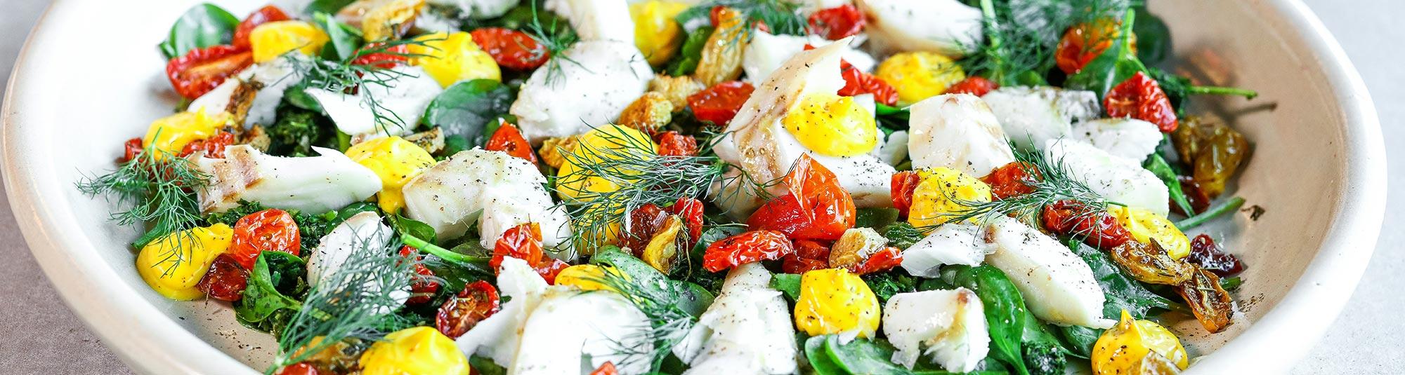 Bitar av torskfilé blandat med stekt grönkål och klickar av saffransmajonnäs