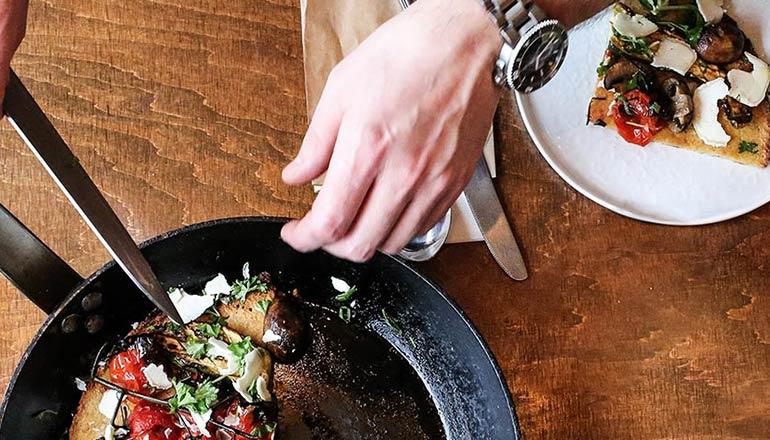 Mörkt bord med stekpanna och god mat som plockas