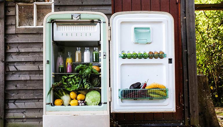 Ett öppet retro kylskåp fyllt med grönsaker utanför gammalt trähus