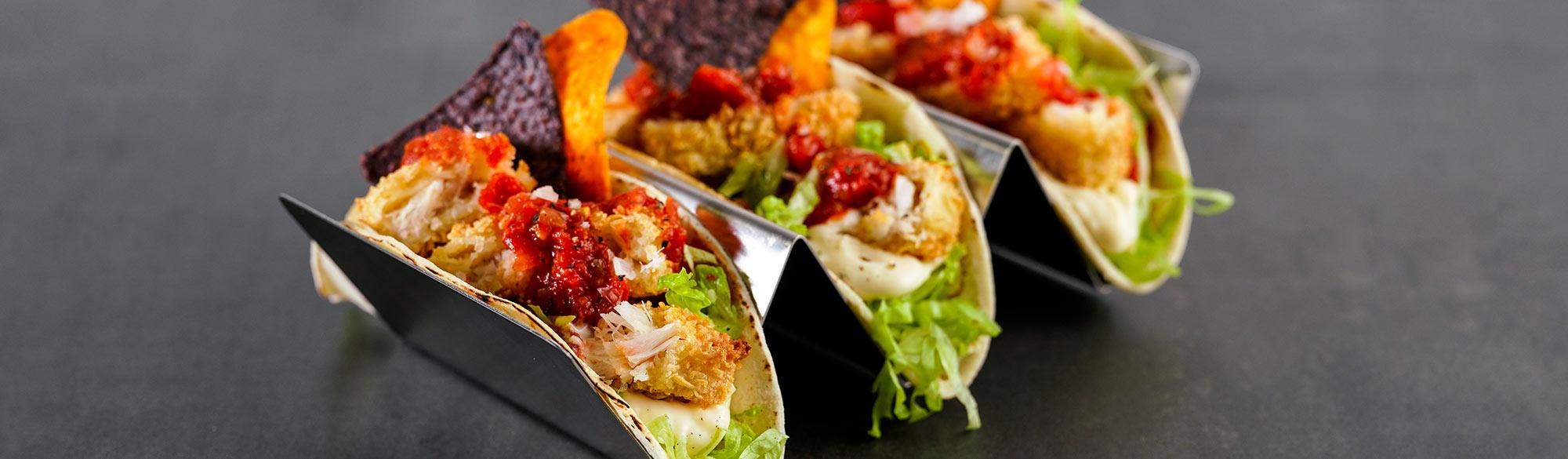 Tre fisktacos i serveringsställ. Delade fiskpinnar, sallad, salsa och nachos.
