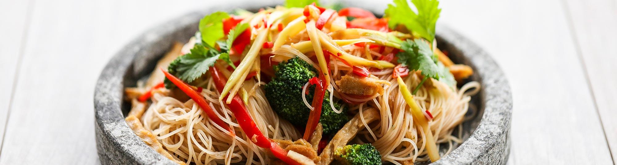 En wok med Pease strimlor, risnudlar, röd paprika och broccoli.