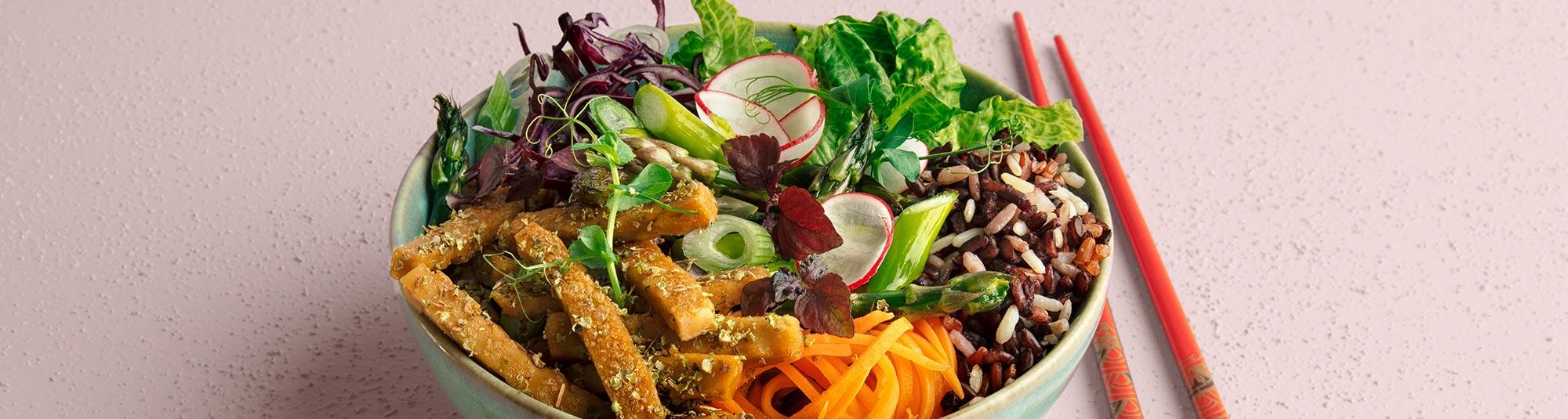 Bowl med veganska Pease strimlor, rismix och örtolja.