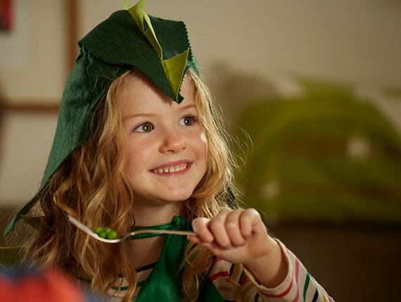 Kleines glückliches Mädchen mit Erbsen auf einer Gabel