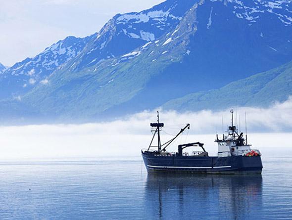 Ein in Meer liegendes Schiff vor Gebirge