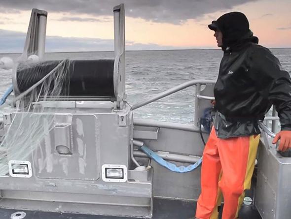 Mann mit wasserfester Kleidung auf einem Schiff