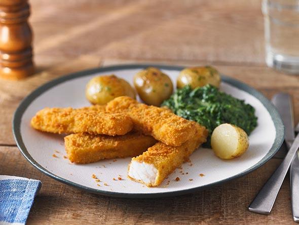 Fischstäbchen mit Kartoffeln und Spinat auf einem Teller