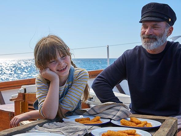 Ein älterer Mann und ein kleines Mädchen sitzen an einem Tisch