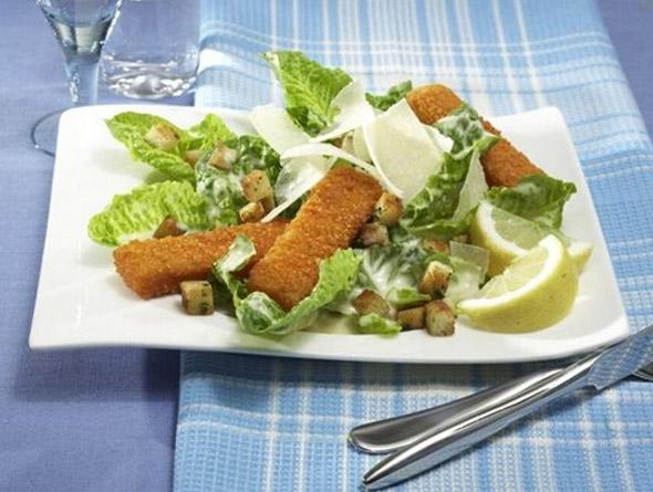 Fischstäbchen mit Salat und Zitrone auf einem Teller