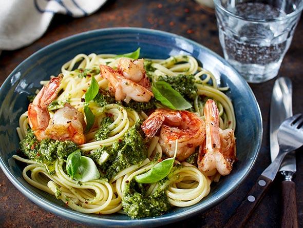 Teller gefüllt mit Pasta Garnelen Grünkohl und Pesto
