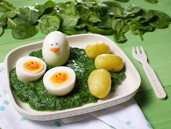 Kinderteller mit Rahmspinat Kartoffeln und Eiern mit Gesicht