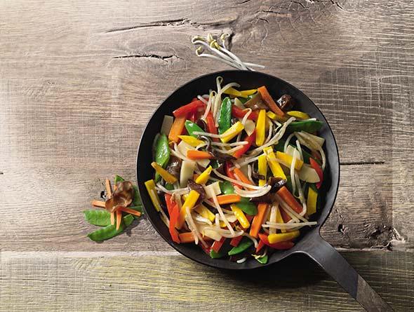 Wokgemüse in Bratpfanne auf Holztisch
