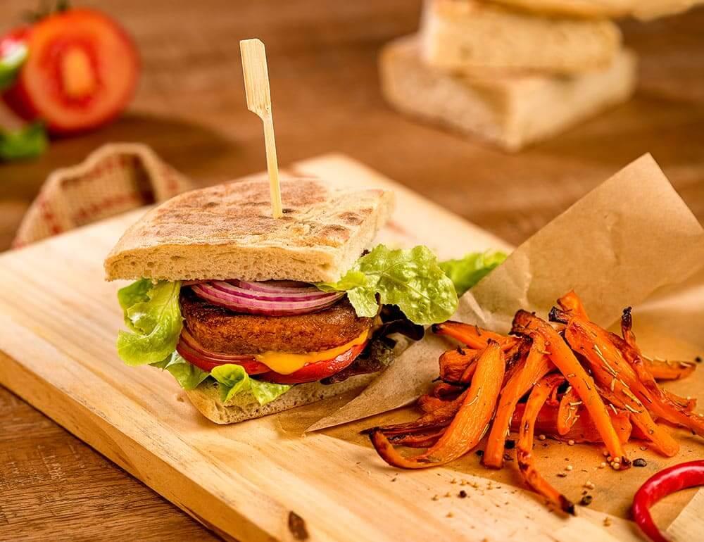 Burger de proteína vegetal em bolo do caco com chips de cenoura e molho de mostarda de mel