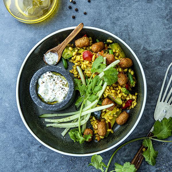 Hvetekornspilaff med grønnsaker, mini blouletter, agurk og tzatziki, servert i en bolle pyntet med mynteblader