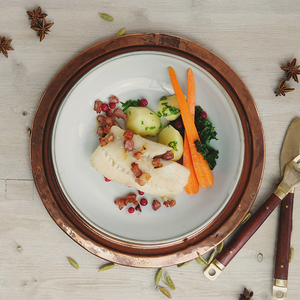 Torsk med bacon, poteter, gulrøtter og grønnkål på tallerken med bestikk på siden