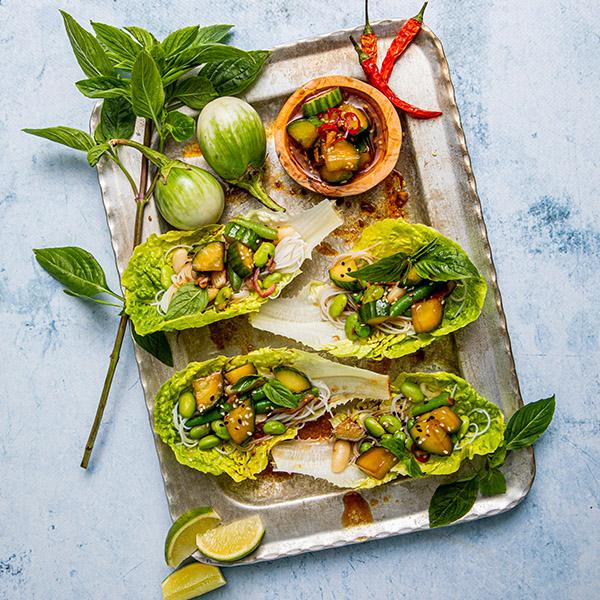Salatblader fylt med bønnemiks og nudler på fat
