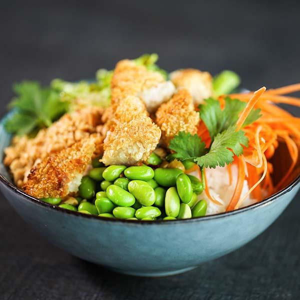 Poke bowl med sprø fisk, soyabønner, gulrot, salat og koriander.