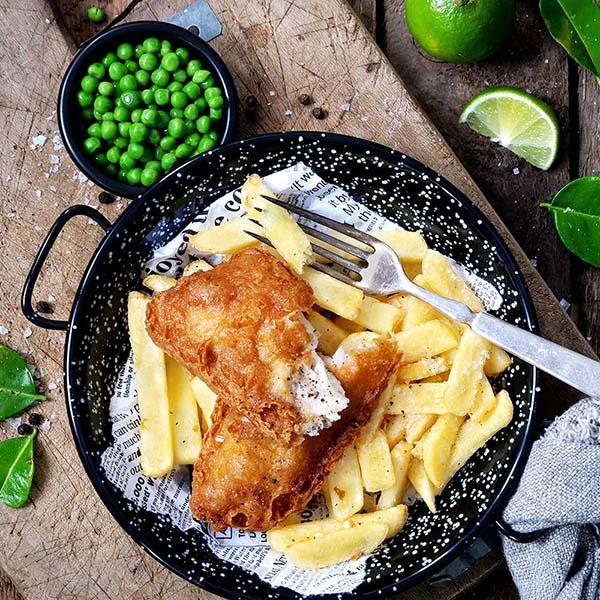 Fish 'n chips anrettet på tallerken med lime og grønne erter ved siden av.