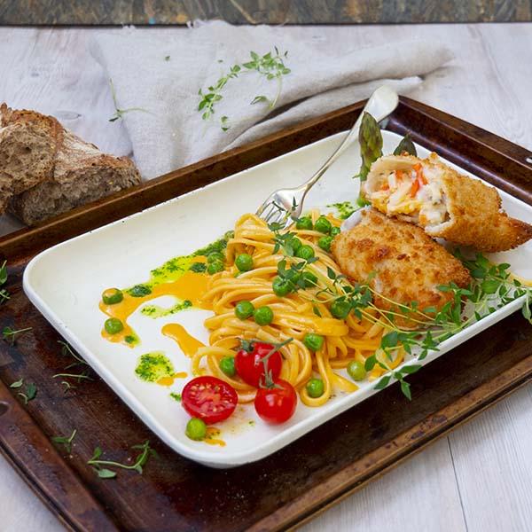 Sprøbakt fiskerullade Julienne anrettet på tallerken med pasta i skalldyrsaus, erter og cherrytomat