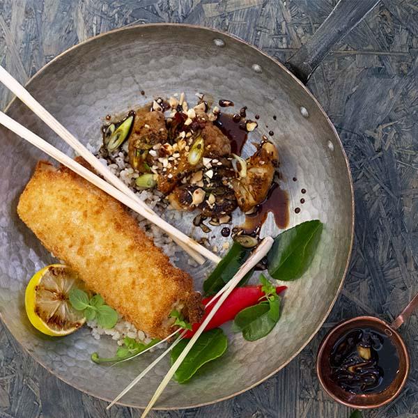 Sprøbakt fiskerullade på tallerken med stekt blomkål i teriyaki-saus, drysset med ristede cashewnøtter