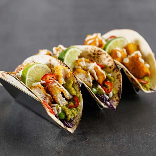 Stativ med små tortilla fylt med fisketaco; fiskepinner, guacamole, erter, rødkål, chili, limebåt