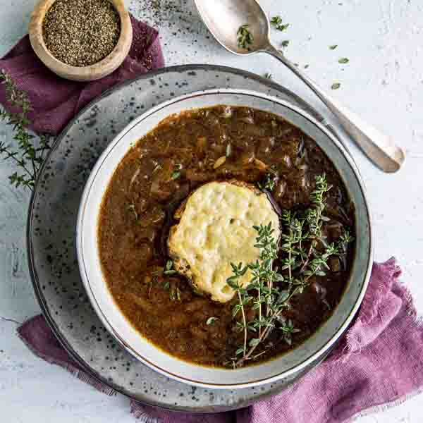 Løksuppe i bolle med en brødskive og fersk timian på toppen