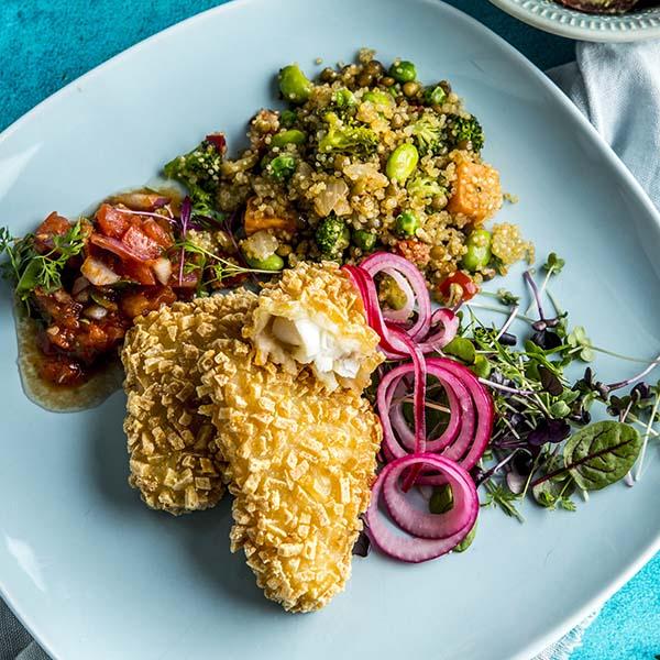 Røstipanert fisk anrettet på tallerken med quinoapilaff, salsa, salat og syltet rødløk.