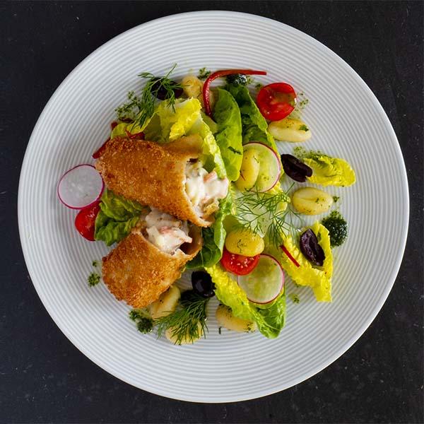 Sprøbakt fiskerullade anrettet på tallerken med gnocchi, hjertesalat, reddik og cherrytomat.