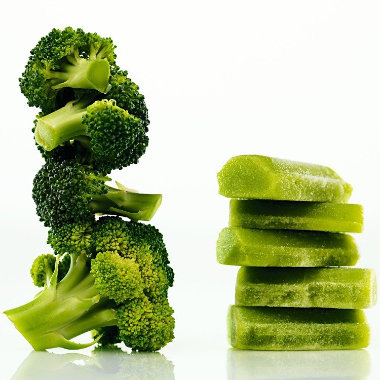 Fryst broccolipuré med färsk broccoli staplad på hög