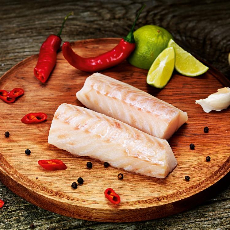 Ryggbitsfilé av torsk på en runt skärbräda med chili och lime