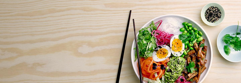 Pease teriyaki bowl med sesamfrön och koriander på plywood