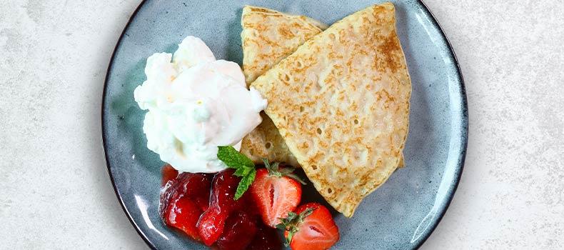 Dubbelvikta pannkakor med grädde jordgubbssylt och jordgubbar