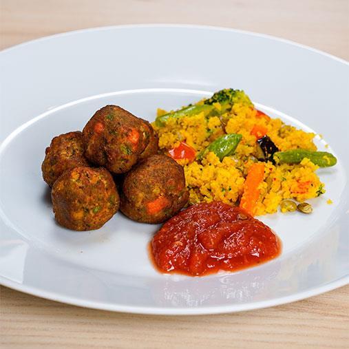 Grönsaksbullar med tomatsås på en bädd av couscous