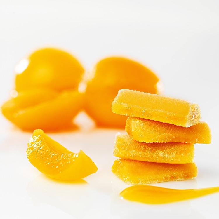 Fryst aprikospuré i pelletsform med aprikoser i bakgrunden