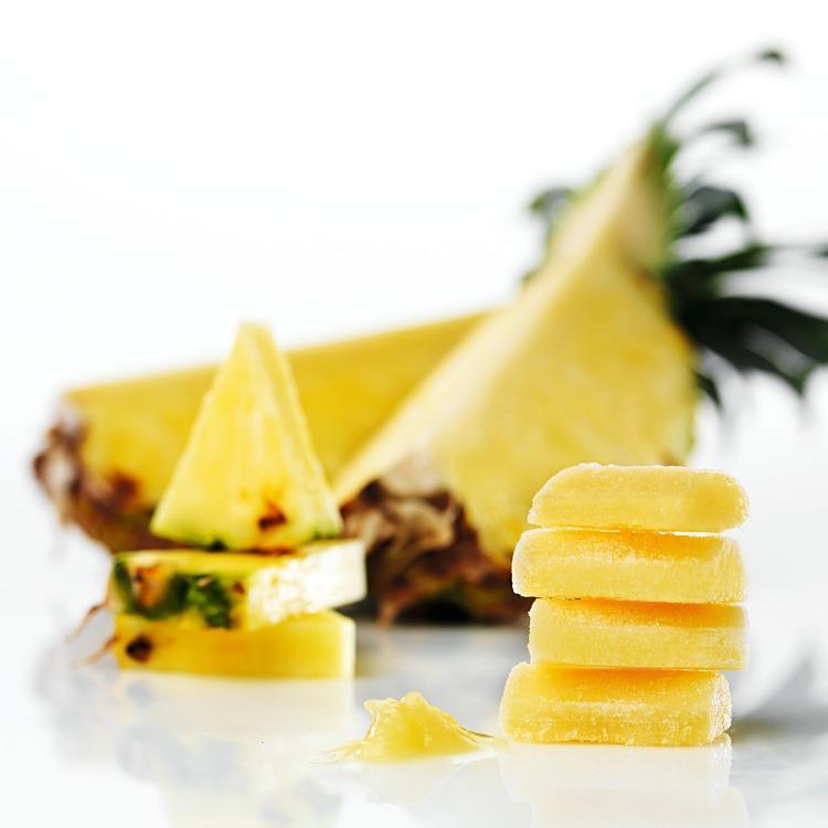 Fryst ananaspuré i pellets med skivad ananas i bakgrunden