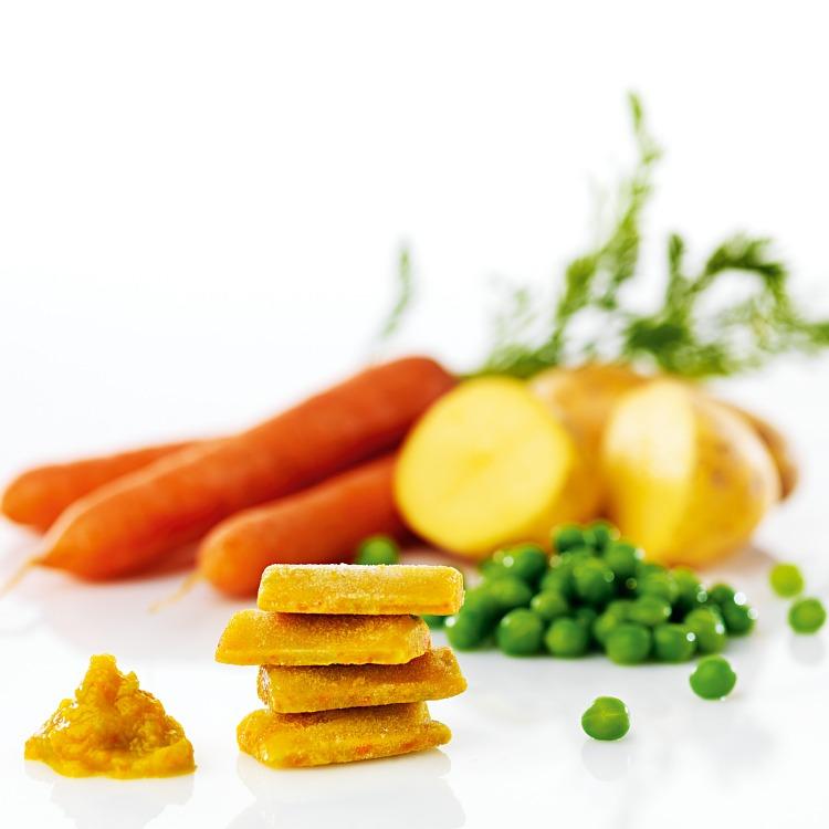 Fryst grönsakspuré i pelletsform med grönsaker som morot potatis och ärter i bakgrunden