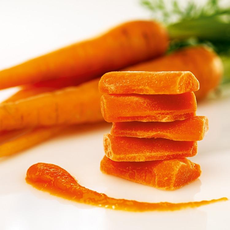 Fryst morotspuré i pelletsform med färska morötter i bakgrunden