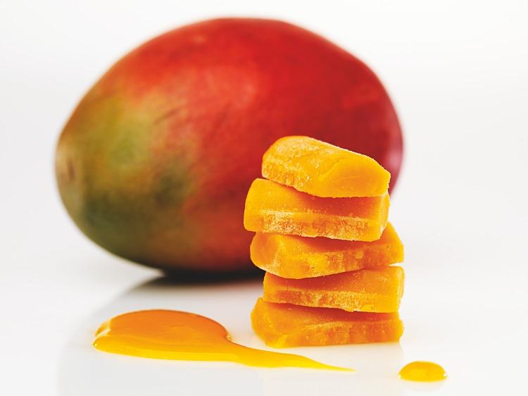 Torn av pellets av fryst mangopuré med en färsk mango bakom sig
