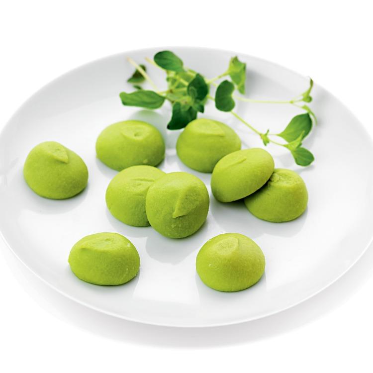 Små gröna bollar ärtimbal en vit tallrik