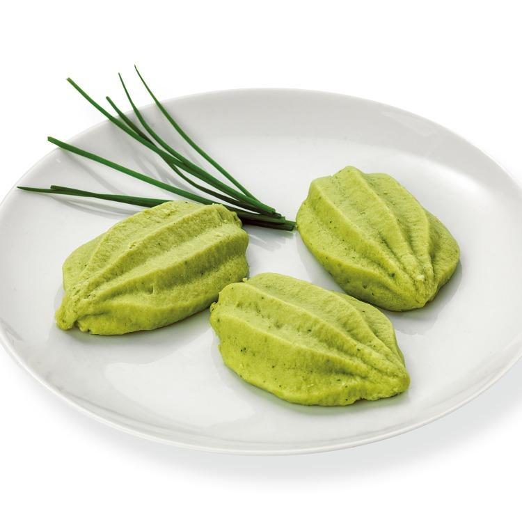 Läckert spritsad broccolitimbal på en vit tallrik med gräslök