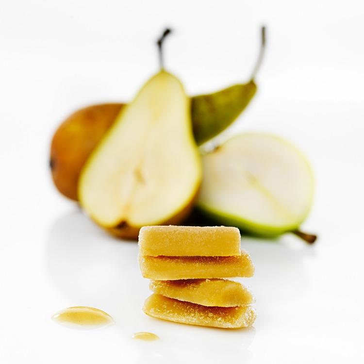 Fryst päronpuré i pelletsform med skurna päron i bakgrunden