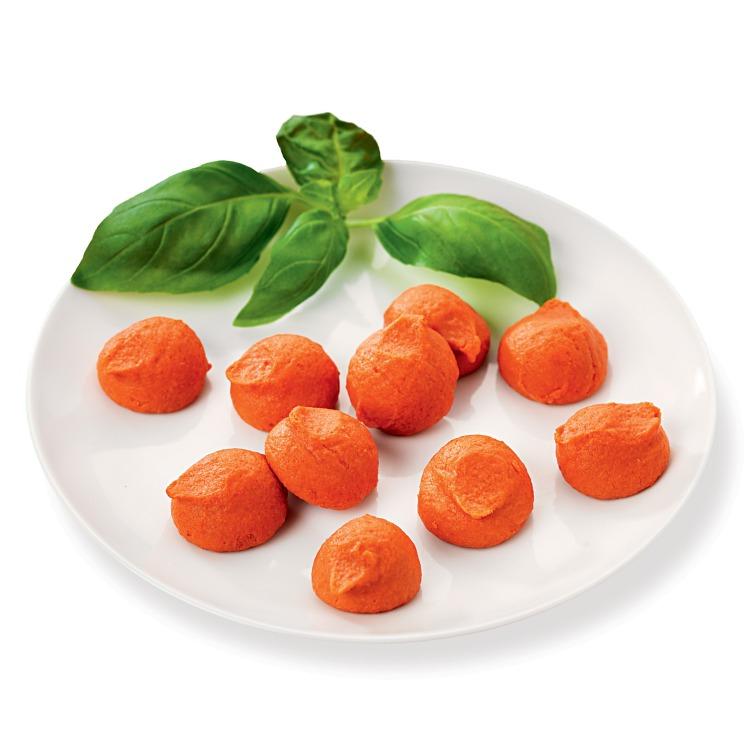 Små röda bollar av tomattimbal på en vit tallrik med blad av basilika