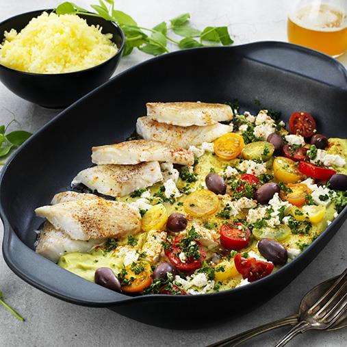 Bitar av fiskfilé med ärtkräm, fetaost och oliver i en stor form.